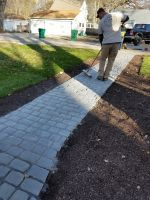 Applying the finishing layer of sand to this courtstone path at the Chain of Lakes waterfront remodel